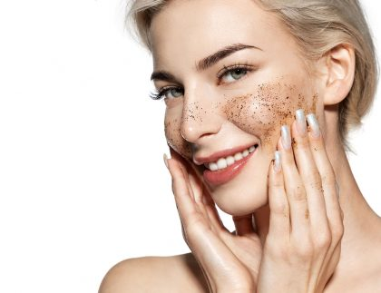 Portrait of lovely model scrubbing skin with cleansing lotion.